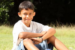 School boy sitting in the park on sunny day Royalty Free Stock Image