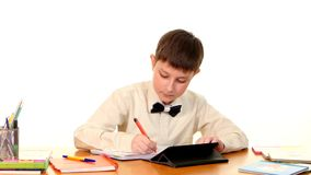 School boy sitting, thinking and writing homework stock footage