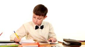 School boy sitting, thinking and writing homework stock video