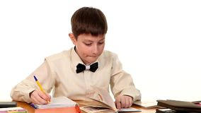 School boy sitting, thinking and writing homework stock video footage