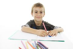 School boy sitting and writing in notebook. Isolated on white Royalty Free Stock Photography