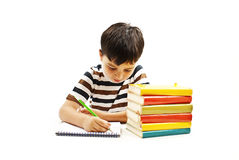 School boy sitting and writing in notebook Stock Photos