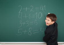 School boy solve math on school board Stock Photos