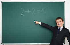 School boy solve math on school board Stock Photo