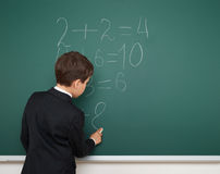 School boy solve math on school board Royalty Free Stock Image