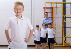 School boy standing in gymnasium with teacher and classmates watching Stock Photo