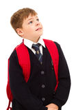 School boy standing and looking up. School boy standing and looking up with his backpack. Wearing in school uniform. Isolated on white Royalty Free Stock Photo