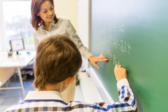 School boy with teacher writing on chalk board Stock Image