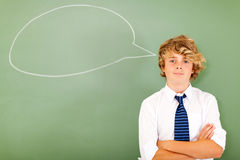 School boy thinking. Young high school boy in front of chat box drawn on chalkboard thinking Royalty Free Stock Images