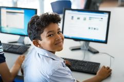 School boy using computer. Young happy schoolboy using computer to search internet. Arab child learning to use computer at elementary school. Portrait of smiling Royalty Free Stock Photo