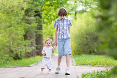 School boy walking with his little sister in a park Stock Photos