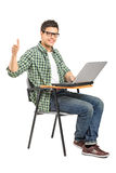 School boy working on a laptop and giving thumb up. A school boy working on a laptop and giving thumb up  on white background Stock Photo