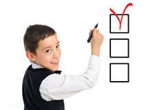 School boy wrighting checkboxes with pen. Portrait of a young school boy wrighting or drawing checkboxes with black point pen isolated on white background Stock Photos