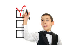 School boy wrighting checkboxes with pen. Portrait of a young school boy wrighting or drawing checkboxes with black point pen isolated on white background Royalty Free Stock Photo