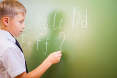 School boy writes English alphabet with chalk on blackboard Royalty Free Stock Photos