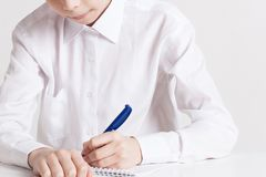 School boy writes in notebook at the table stock image
