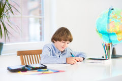 School boy writing his homework at white desk Royalty Free Stock Photography