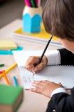 School boy writing in notebook Stock Image