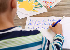 School Boy Writing on Paper writing the alphabet with Pencil . Kid, homework, education concept Stock Photos