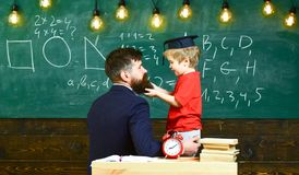 School break concept. Boy, child in graduate cap play with dad, having fun and relaxing during school break. Teacher. With beard, father teaches little son in stock photo