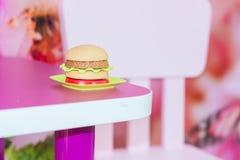 School breakfast. hamburger. malnutrition. On the table with an empty chair Stock Photos