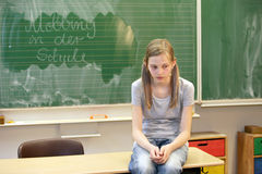 School bullying - horizontal. A sad girl sitting in the classroom at school in front of a blackboard with the words bullying at school Stock Photos