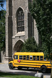 School bus. Typical yellow school bus in front of a gothic style school building royalty free stock photo