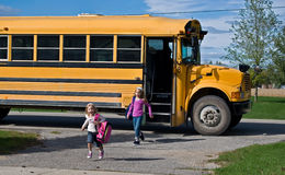 Little girls with school bus. Little girls getting off the school bus Stock Photography