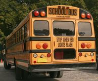 School Bus. Back view of yellow school bus, showing red lights, warning signs, windows stock photo