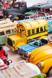 School bus. Handmade unique miniature model of oldtimer yellow school bus toy on a table, with turkish blue eye amulet instead headlights and many more oldtimer Stock Image