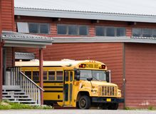 School bus. Yellow school bus parked in front of school royalty free stock images