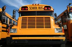 School bus. The front view of a yellow public school bus with a blue sky background and 2 buses on either side stock photo