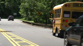 School bus and cars driving by stock video footage