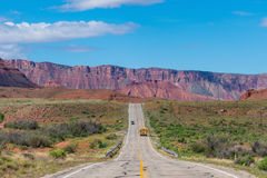 School bus on a desert highway in southern Utah. Yellow school bus traveling the highway in southern Utah`s canyon country Royalty Free Stock Photography