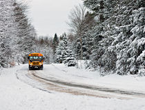 School Bus Driving Down A Snow Covered Rural Road - 1 Stock Image