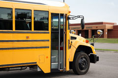 School bus in front of an elementary school. School bus waits fro students at the end of the school day Royalty Free Stock Photos