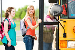 School Bus: Girl Looks to Side While Boarding Bus. Series with multi-ethnic group of teenage students boarding and on a school bus. Students boarding the bus stock photos