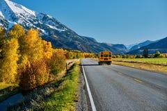 School bus on highway in Colorado at autumn. School bus on highway in Colorado Rocky Mountains at autumn, USA. Mount Sopris landscape stock image