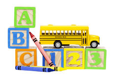 School Bus Learning Blocks. A miniature school bus atop numbered learning blocks with alphabet learning blocks and primary colored crayons to stacked to left Royalty Free Stock Photography