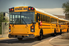 School Bus. In a line outside education facility Stock Images