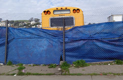 School Bus in Repair Yard. Broken down school bus behind chain link fence Royalty Free Stock Photography