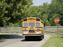 School Bus on the Road. School Bus stopped at a neighborhood stop sign stock image