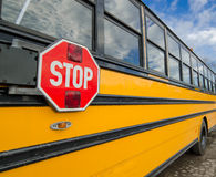 School bus safety. A close up of side of a school bus with stop sign in foreground royalty free stock image
