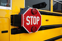 School bus stop. Side view of a school bus and its the stop signal stock images