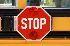 School Bus Stop Sign. A big red stop sign on the side of a  yellow school bus Stock Images