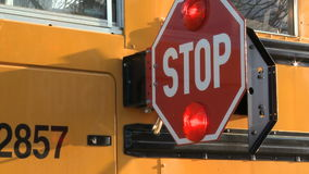 School bus stop sign. Two takes of the stop sign on a school bus swinging out to signal drivers to stop for school children stock video
