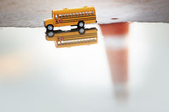 School bus toy model and water reflection. Stock Photography
