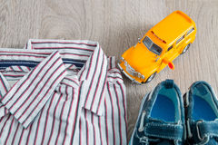School bus toy near shirts and blue boat shoes on grey wooden background. Boy outfit. Close up. Royalty Free Stock Image