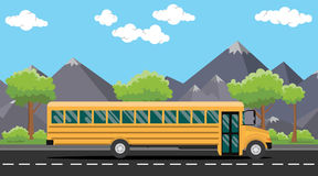 School bus yellow on road with tree and mountain as background Royalty Free Stock Image