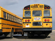 School Buses - back end. This is a clos-up view of the back end of a school bus and the side view of another school bus parked next to it Stock Image